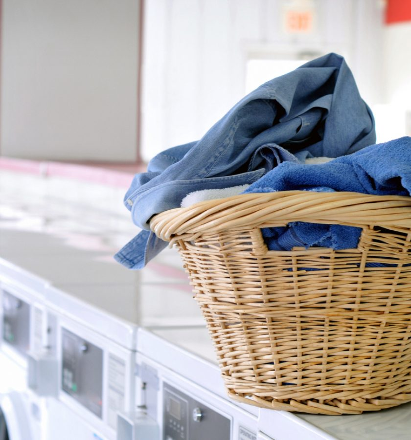 Horizontal image of a basket of laundry waiting to be washed at the laundromat. Background light is intentionally overexposed. A small amount of grain has been added to the background.